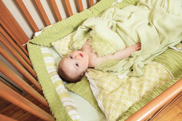 Overhead view of cute baby boy lying under blankets in wooden