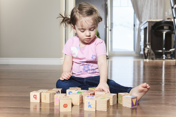 beautiful little girl playing with blocks on floor