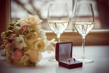 Свадебные кольца в коробочке, букет невесты и бокалы с вином