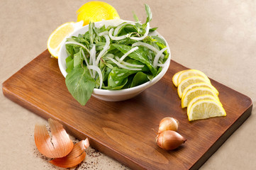 Rucola salad leaves with ingredients on a wooden plate