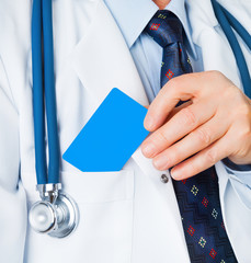 Closeup of business card in doctor's hand, and doc put the card