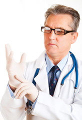 Male doctor putting on protective gloves on white background