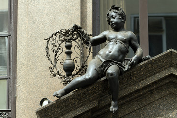 Black sculpture of a boy with flowers on one of the roofs of Vie