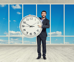 man with big white clock standing