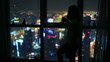 women drinking and watch aerial night city at luxury home