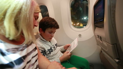 mother and son checked safety card in aircraft cabin