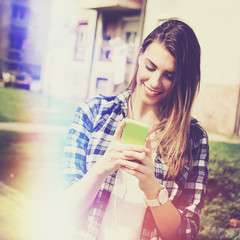 Teenage girl with smartphone texting in park in summer