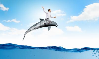 Man saddling dolphin