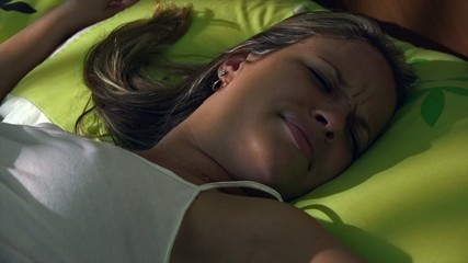 Young Woman In Bed Waking Up At Morning Snoozing Alarm Clock
