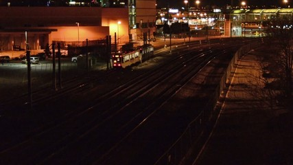 A commuter train going through the train yards at night