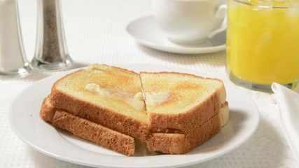 A plate of hot buttered toast being set on the table