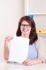 Plump woman at a table holding a white sheet of paper with copy