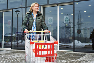Woman with shopping cart exits the store