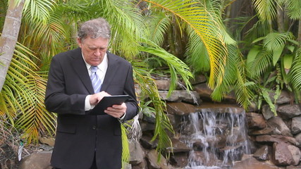 Businessman standing using his tablet by a waterfall