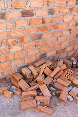 pile of bricks in construction site with brick wall background