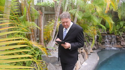 Businessman walks by a swimming pool with a tablet.