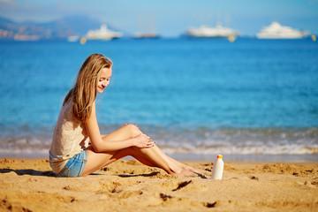 Beautiful woman applying sunscreen on her legs