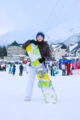 Обаятельная девушка со сноубордом в горах
