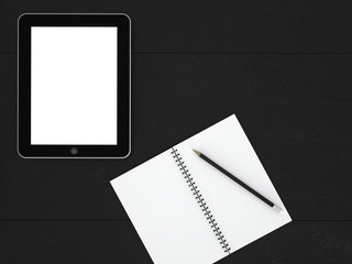 Open notebook and tablet on a black desk