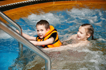 Boy and girl swimming in jacuzzi