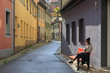 Teenage girl sitting on the bench on old city street