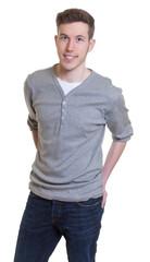 Stehender junger Mann im grauen Shirt