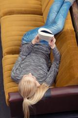 blonde frau liest ein buch auf dem sofa