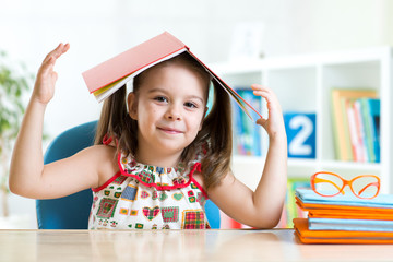 preschooler  kid girl with book over her head