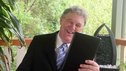 Businessman laughing with tablet sitting in a chair