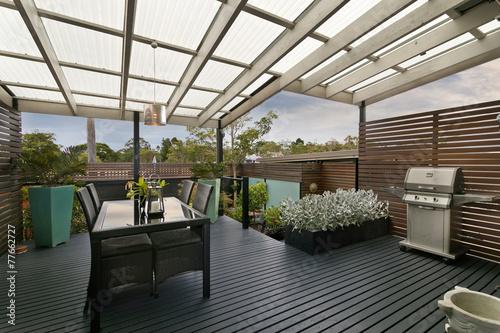 Leinwanddruck Bild backyard cozy patio area with wicker furniture set
