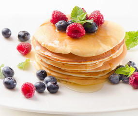 pancakes with raspberries and blueberies on  white plate