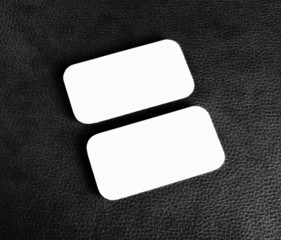 Blank business cards with rounded corners on a black leather bac