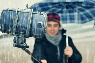 young man taking a selfie under the rain