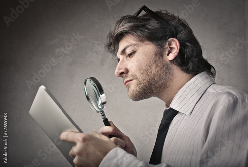 Businessman reading a contract - 77665948