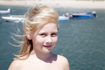 Niña rubia con arena en la cara y barcas al fondo