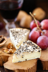White mold French cheese like Brie with grapes and walnuts