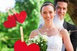 Composite image of smiling bride and groom in garden