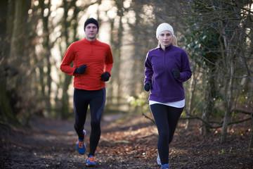 Couple On Winter Run Through Woodland