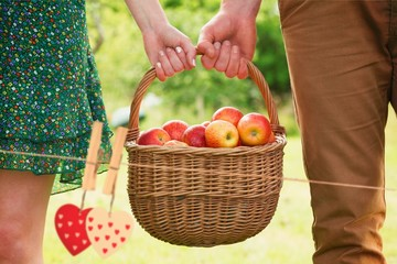 Basket of apples being carried by a young couple