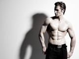 Handsome muscular young man posing at studio.