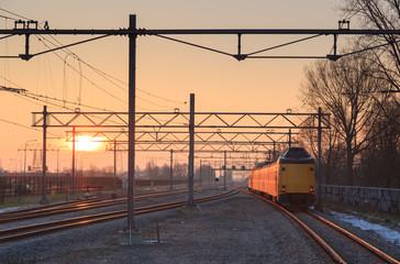 Passenger train and railroad tracks during sunrise.