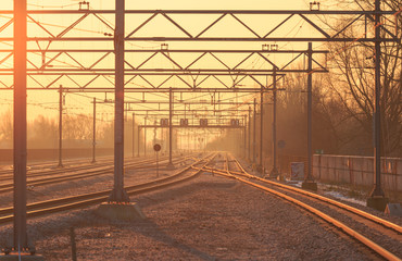 Empty railroad tracks during sunrise.