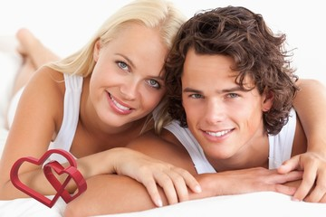 Composite image of couple lying on their bed