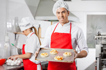 Smiling Chef Holding Small Pizzas On Baking Sheet At Kitchen