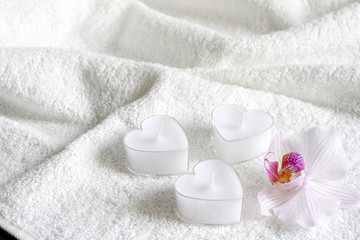 Candles on white towel abstract body care spa background