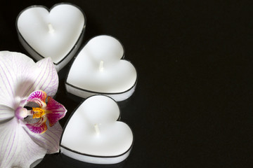 Candles hearts with orchid on black background love concept