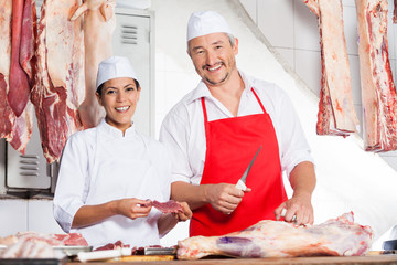 Butchers Working At Counter In Butchery