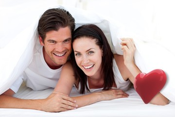Composite image of happy couple lying on bed
