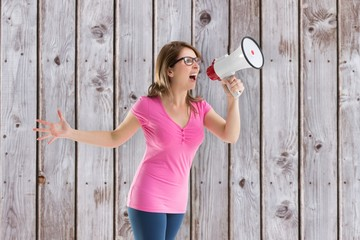 Composite image of angry woman with megaphone and glasses