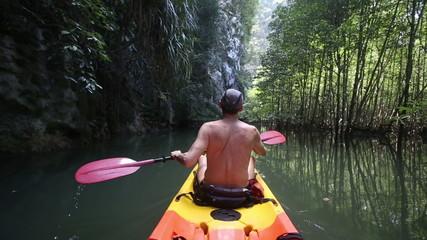 topless elder man floating in kayak in lagoon past cliff